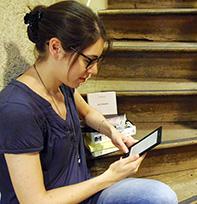 Jeune femme lisant sur une  liseuse dans les escaliers