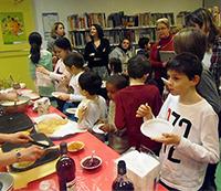 Enfants et adultes mangeant des crêpes à la bibliothèque jeunesse