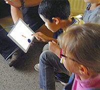 Petit garçon qui interagit sur une tablette numérique à la bibliothèque des Prés Saint-Jean