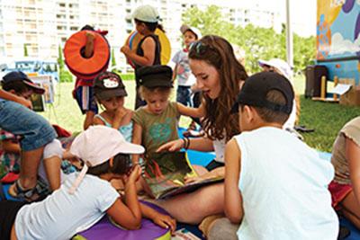 Enfants et jeune fille lisant et jouant dehors près du bibliobus