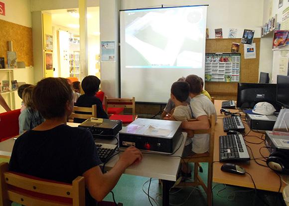 Groupe d'enfants devant une vidéo projection située dans l'espace multimédia