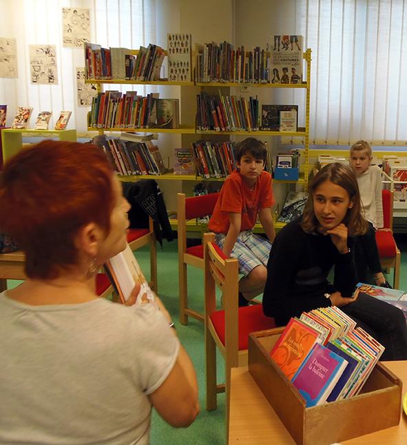 3 enfants écoutent les propositions de lecture d'une bibliothécaire